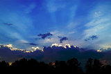 Photo of a sunset highlighting the outline of the clouds in a sky that is deep blue.