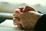 Hands clasped in prayer resting on the bible.